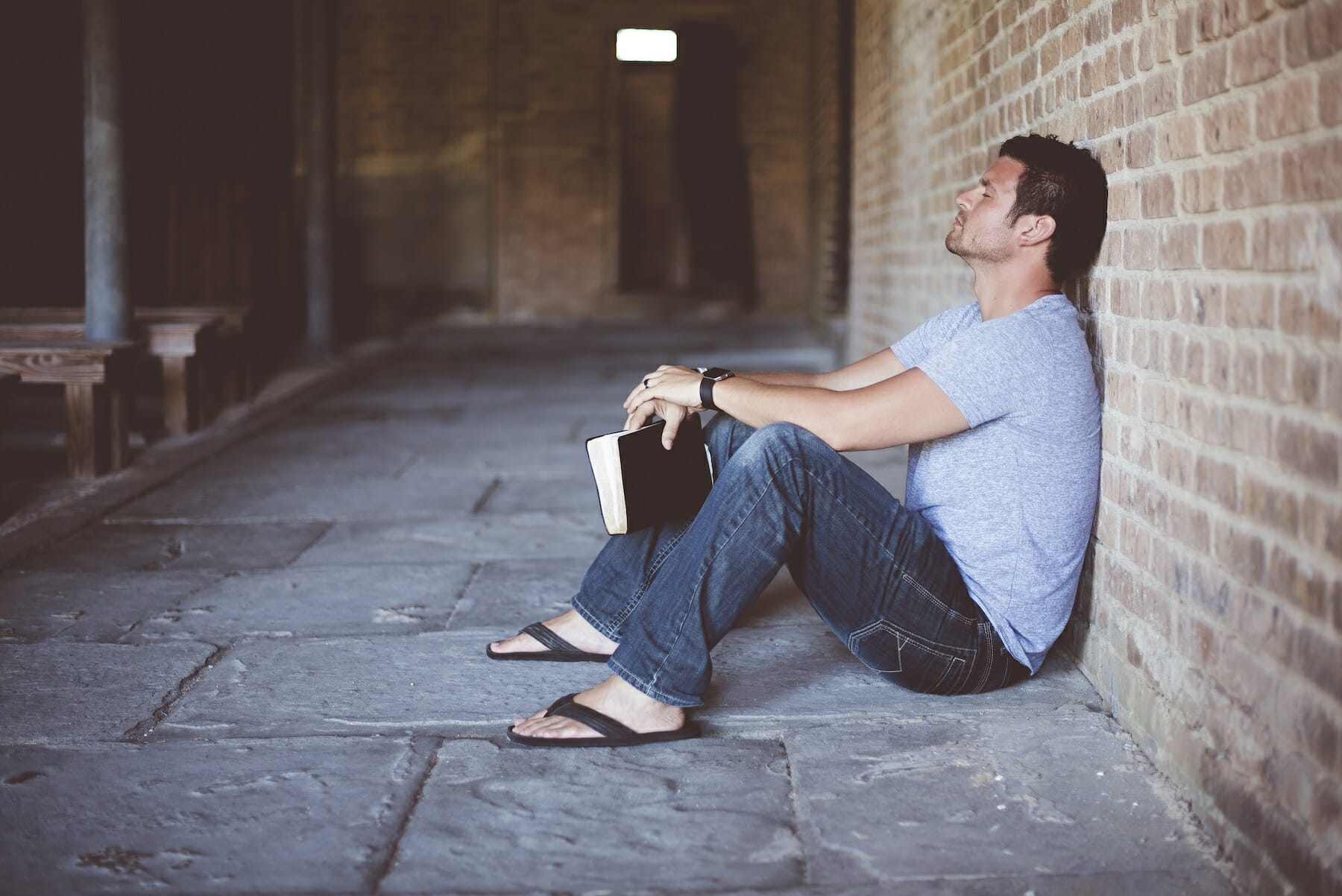 Man holding book frustrated against wall.