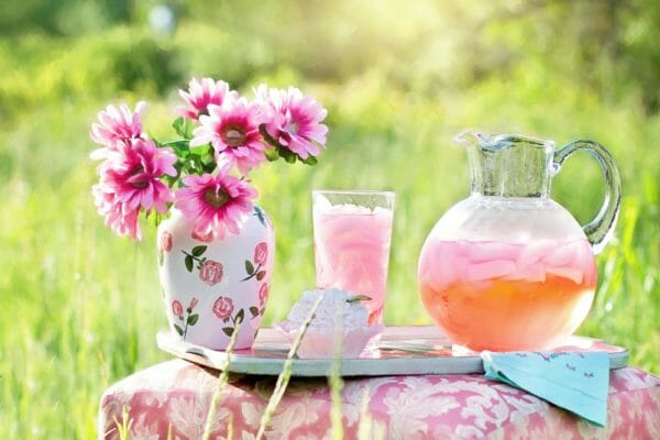 Flowers and iced drink on table.