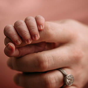 Baby holding adult hand with wedding ring